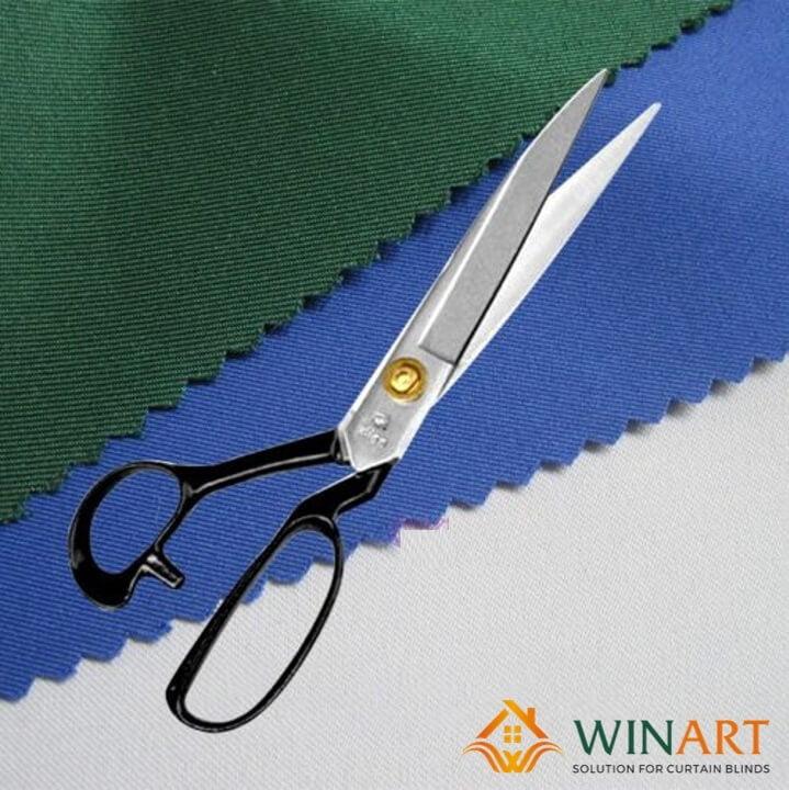 Dùng kéo để cắt vải may rèm cho vừa với cửa